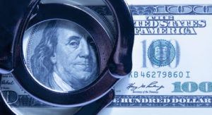 Dollar cash and handcuffs as symbol of corruption in the judicial system, justice, law, bail, crime, bribing and fraud.